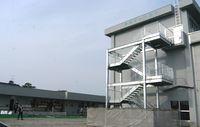 津波避難を想定して屋外階段が増設されている。奥はサッカー協会も入居するクラブハウス